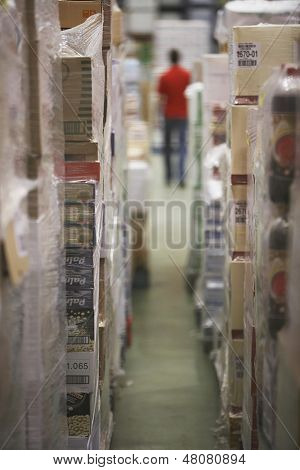 Warehouse full of cellophane wrapped goods with blurred man in the background