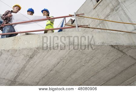 Low angle view of construction team examining building plans at site