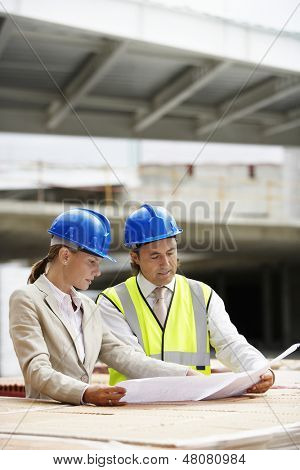Architect and construction manager reading blueprint at site