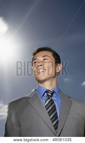 Low angle view of a smiling young businessman standing against sky