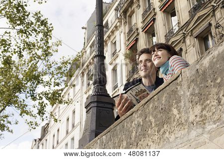 Low angle view of a smiling couple looking over bridge with guidebook
