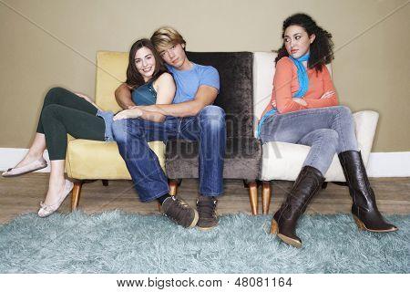 Joven mujer sentada con los brazos cruzados por abrazar el par en el sofá