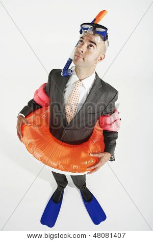 Elevated view of a businessman in flippers; inflatable rubber ring; snorkel and goggles against white background