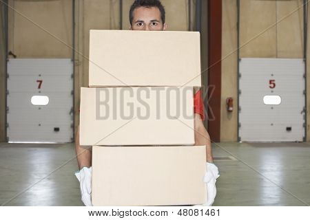 Warehouse worker carrying boxes against loading dock doors