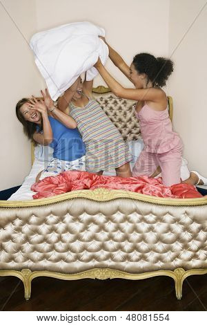 View of three teenage girls pillow fighting on funky bed