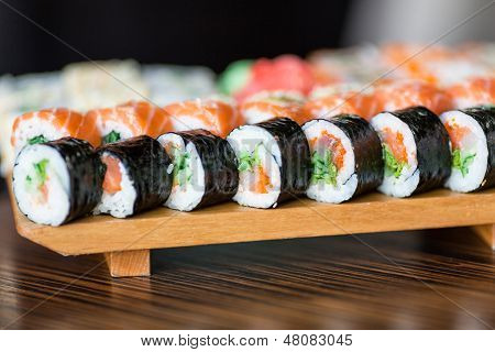 Sushi rolls served on a wooden plate