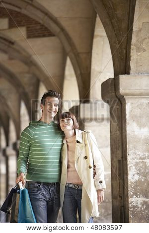 Young couple with shopping bags walking through archway