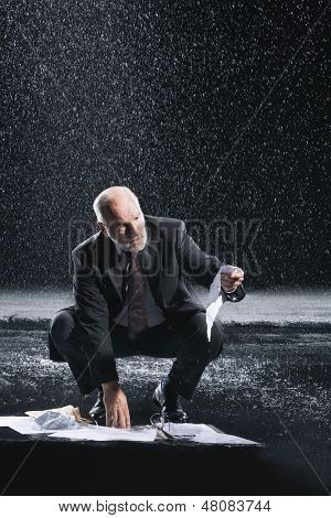 Middle aged businessman picking up soaked documents during downpour