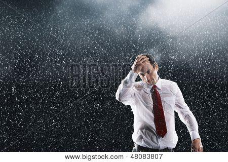 Retrato de un joven empresario corriendo los dedos por el pelo mojado bajo la lluvia