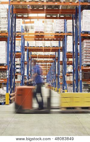 Side view of a blurred man driving pallet jack through warehouse