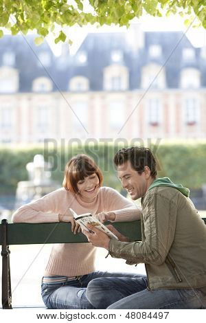Happy young couple reading guide book on city park bench