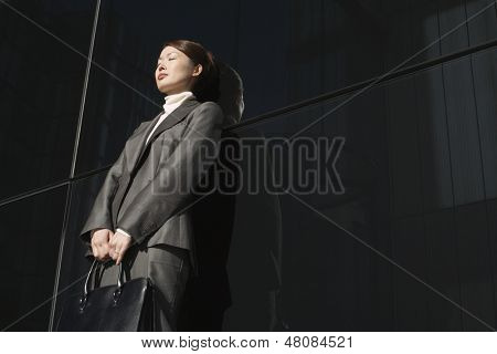 Low angle view of a young businesswoman with eyes closed leaning against office wall outdoors