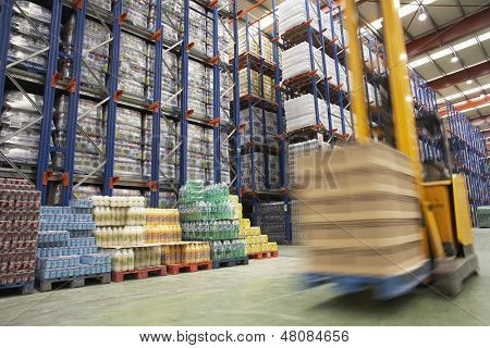 View of speeding forklift in warehouse