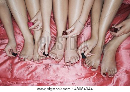 Closeup of teenage girls painting toenails on pink bedsheet