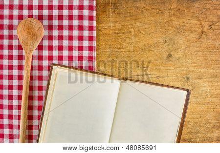 Cuchara de madera y el libro en un tablero de madera con un mantel a cuadros