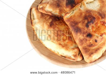 Pizza calzones on wooden board isolated on white