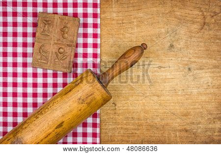 Rolling pin with mold on a wooden board with a checkered tablecloth