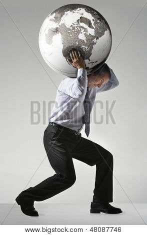Full length side view of a businessman struggling to carry globe on shoulders against gray background