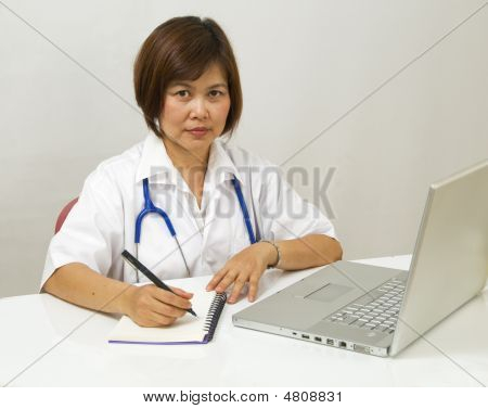 Asian Doctor Sitting At Her Desk And Writing