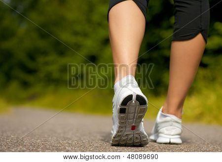 Female Walking Outdoors In Running Shoes