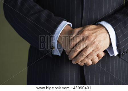 Closeup midsection of a businessman in suit standing with hands clasped