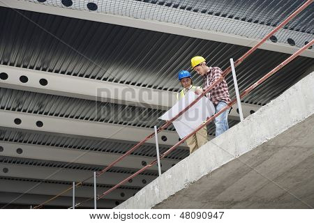 Low angle view of construction manager and worker examining building plans at site