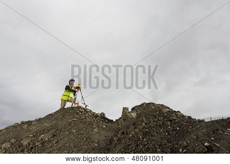 Low angle view of a surveyor using theodolite at site against sky