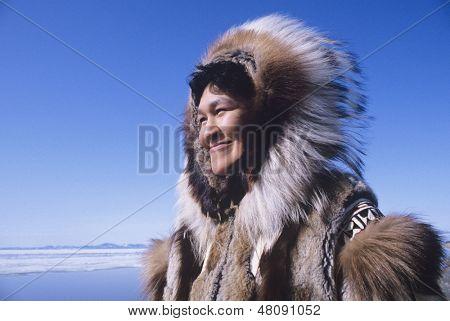 Sorrindo roupas tradicionais vestindo de esquimó mulher vento contra o céu azul claro