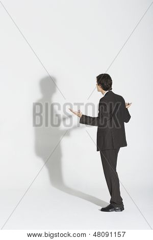 Full length rear view of a young businessman arguing with own shadow against white background
