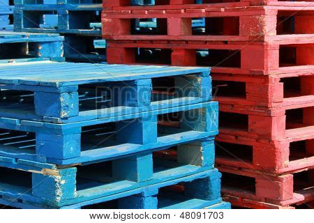 Colorful stacks of red and white crate pallets.
