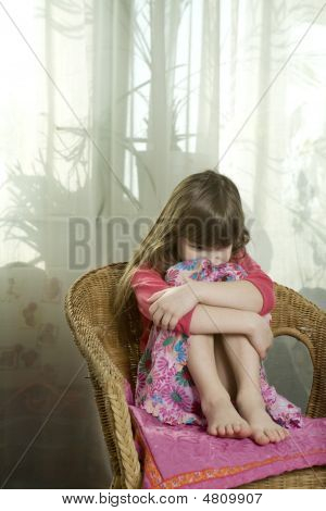 Little Cute Dreaming Girl Sitting On Chair At Window Hugging Her Knees