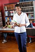 picture of librarian  - Portrait of happy African American librarian holding books while standing in library with students in background - JPG