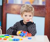 Portrait of unhappy little boy holding blocks in classroom
