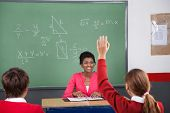 Rear view of teenage girl raising hand while teacher looking at her in classroom