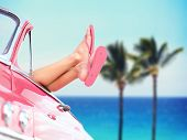stock photo of relaxation  - Vacation travel freedom beach concept with cool convertible vintage car and woman feet out of window against tropical see background with palm trees - JPG