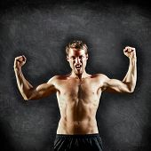 Crossfit fitness man flexing strong and aggressive showing muscles on blackboard background with cop