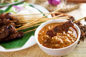 Satay or sate, skewered and grilled meat, served with peanut sauce, cucumber and ketupat. Traditiona