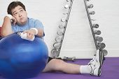foto of fatigue  - Portrait of a wistful overweight man sitting on floor with exercise ball in health club - JPG