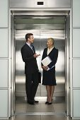 stock photo of elevator  - Happy business colleagues communicating in elevator - JPG