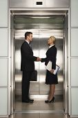 stock photo of elevators  - Profile shot of businessman and businesswoman shaking hands in elevator - JPG