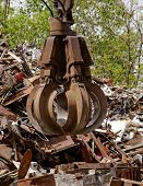 picture of scrap-iron  - inustrial machine with scrap metal grapple in front of scrap iron - JPG