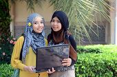 stock photo of muslimah  - beautiful young muslim business woman smile together - JPG