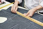 stock photo of measurements  - Tailor hands working with measure bar - JPG