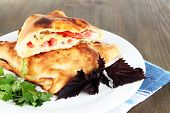 Pizza calzone on plate on napkin on wooden table