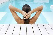 stock photo of pulling hair  - Rear view of young woman in swimming pool at poolside pulling back hair - JPG