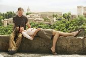 stock photo of lap  - Happy middle aged couple relaxing on wall overlooking Granada - JPG