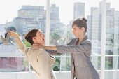 stock photo of strangle  - Businesswomen having a massive fight in a bright office - JPG