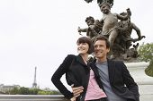 Loving couple standing in front of sculpture
