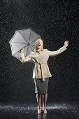 foto of overcoats  - Full length of a young businesswoman in overcoat with umbrella singing in the rain - JPG