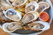 stock photo of shell-fishes  - A platter of fresh raw oysters on ice at an outdoor cafe - JPG